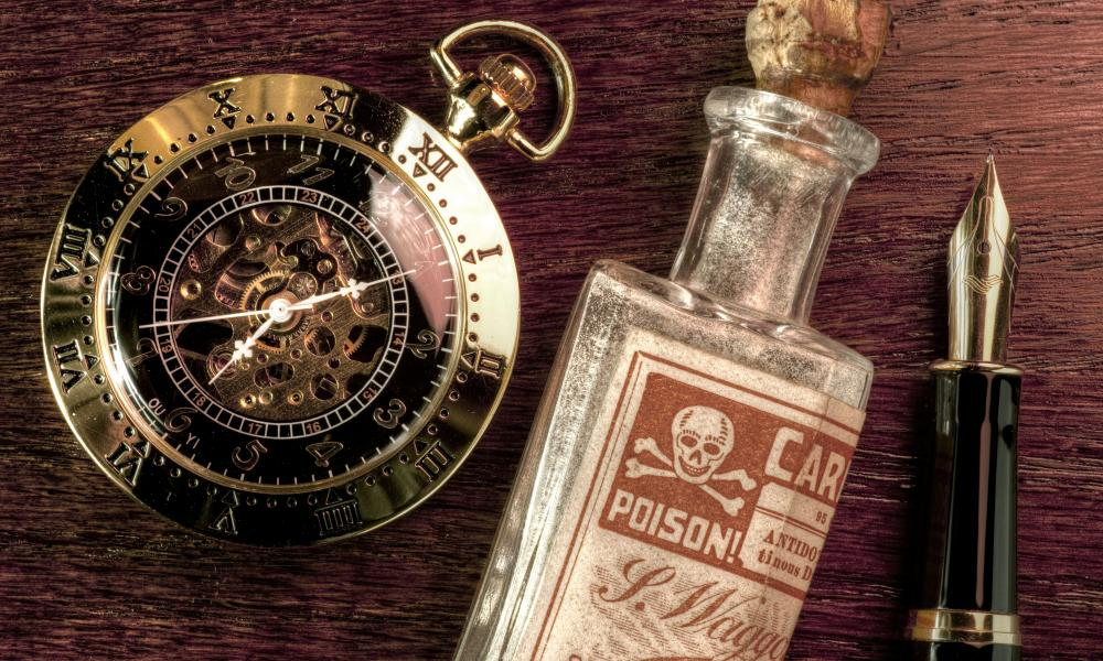 A phial of poison, fountain pen and pocket watch on a wooden desk