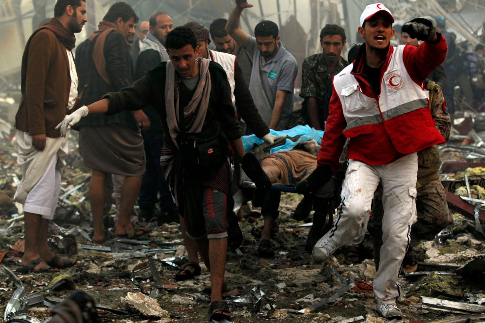 Yemeni rescue workers carry a victim on a stretcher amid the rubble of a destroyed funeral hall building, following reported airstrikes by the Saudi-led coalition on the capital, Sana'a, on 8 October 2016