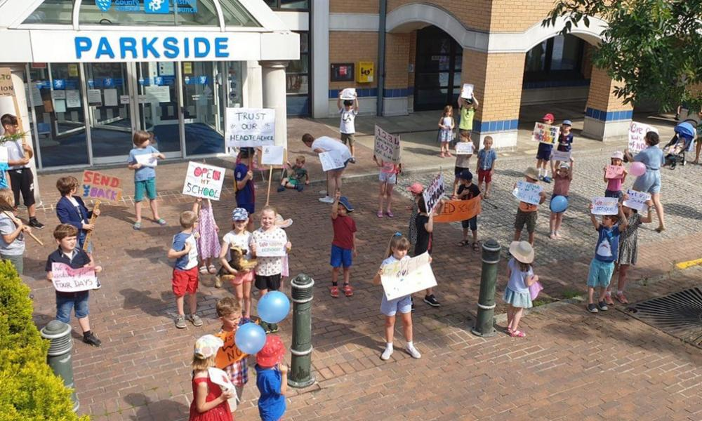 Parents and children stage a protest outside a West Sussex County Council building after plans to get children back to school were rejected.