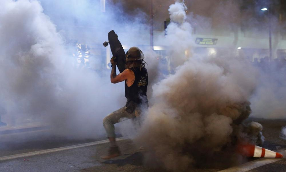A protester shields himself from tear gas with his skateboard in Phoenix, Arizona