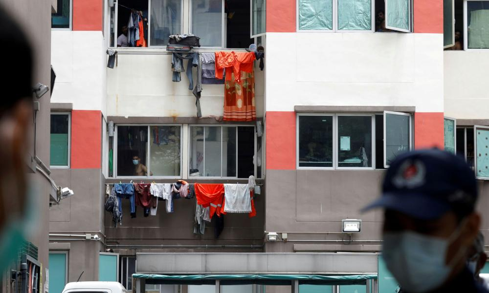 Workers look out of their dorm at Westlite Dormitory, one of the two workers' dormitory gazetted as isolation areas to curb the spread of coronavirus in Singapore.