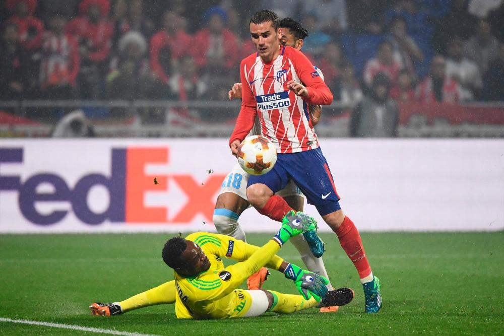 Antoine Griezmann lifts the ball over Marseille goalkeeper Steve Mandanda for his, and Atletico Madrid's, second goal of the game.