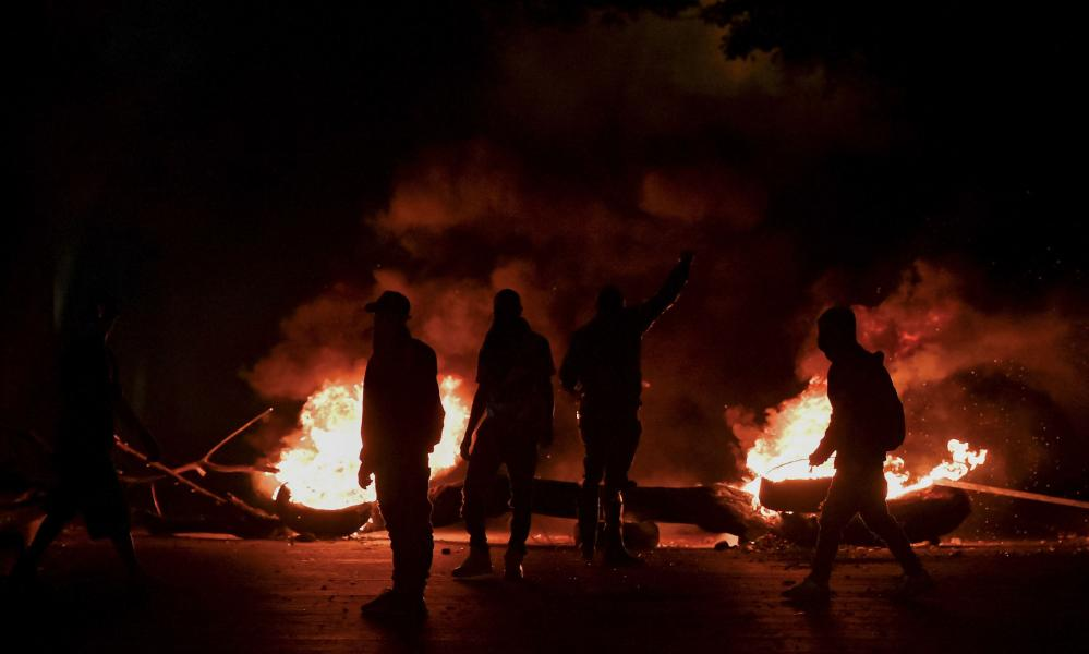 Demonstrators are seen at a barricade as fires burn in Cali on 11 May.