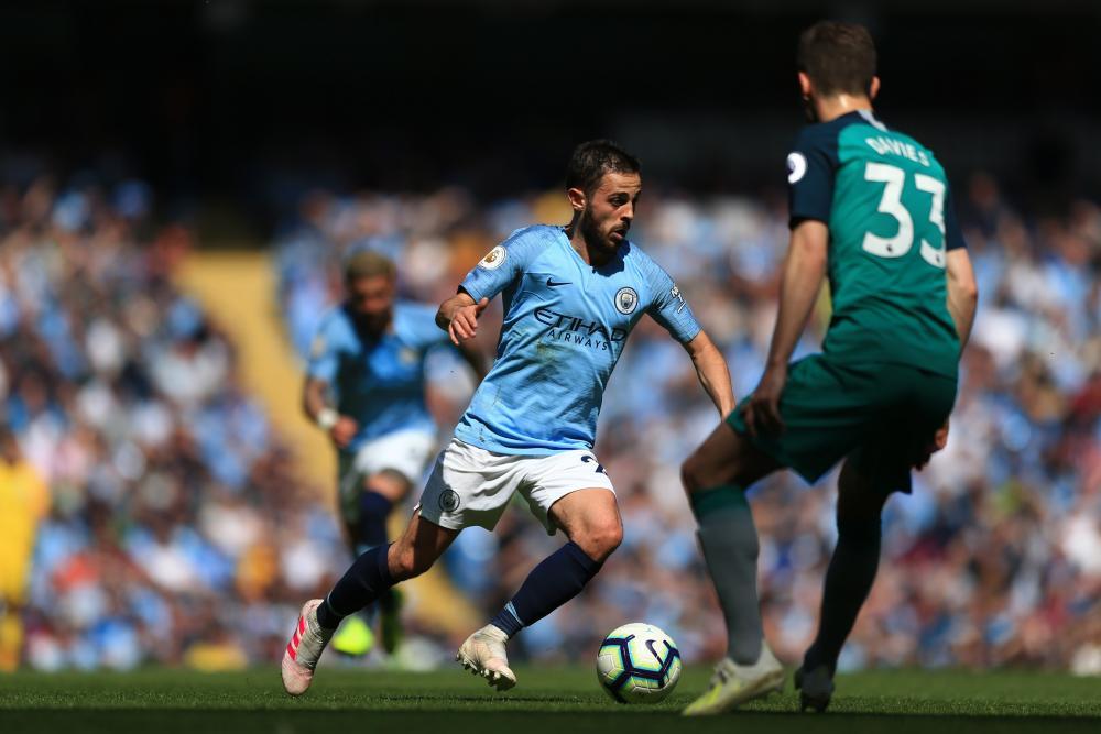 Bernardo Silva of Manchester City runs with the ball as Spurs' Ben Davies looks on.