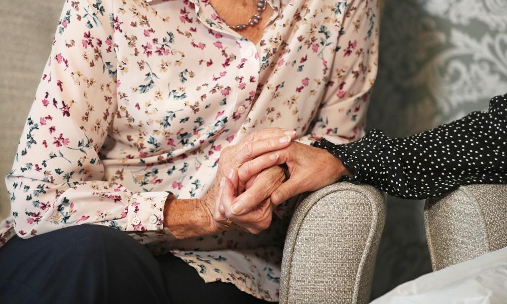 A care home resident holding hands with her daughter