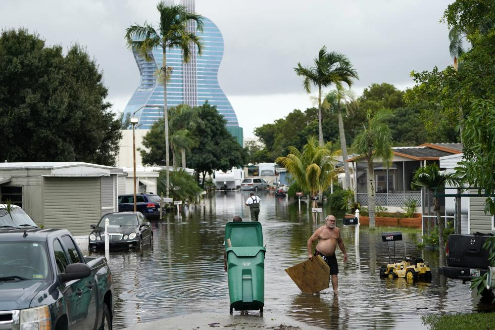 Residents clear debris from a flooded street in the Driftwood Acres Mobile Home Park in the shadow of the Guitar Hotel at Seminole Hard Rock.
