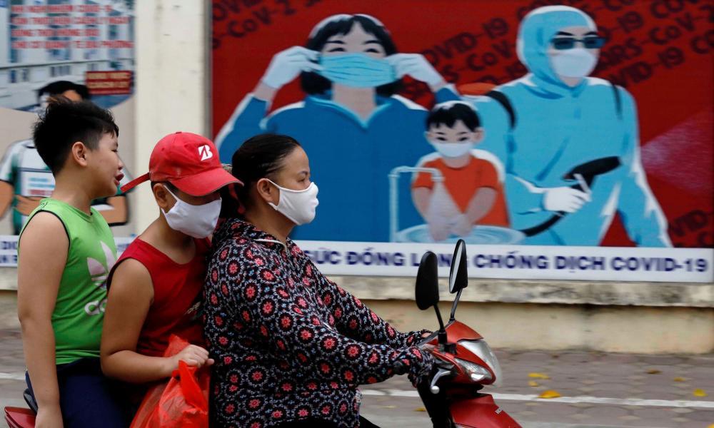 Residents ride past a banner on coronavirus protection in Hanoi