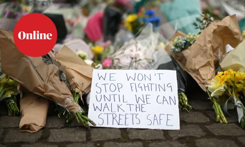 A sign amongst flowers left as a tribute to Sarah Everard in Clapham, London