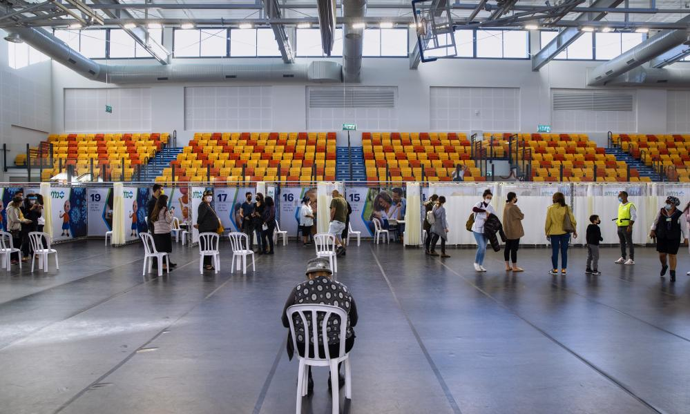 Israelis line up to receive a Pfizer-BioNTech vaccine at a vaccination centre at a gymnasium in Petah Tikva, Israel
