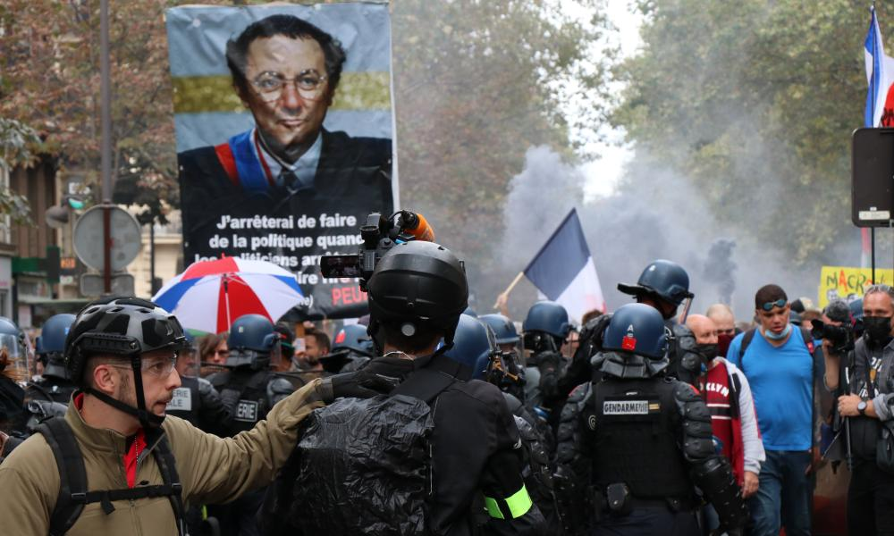 People stage a protest in Paris against compulsory Covid-19 vaccination for certain workers, and the French government's call for the mandatory use of the health pass to access most public spaces.