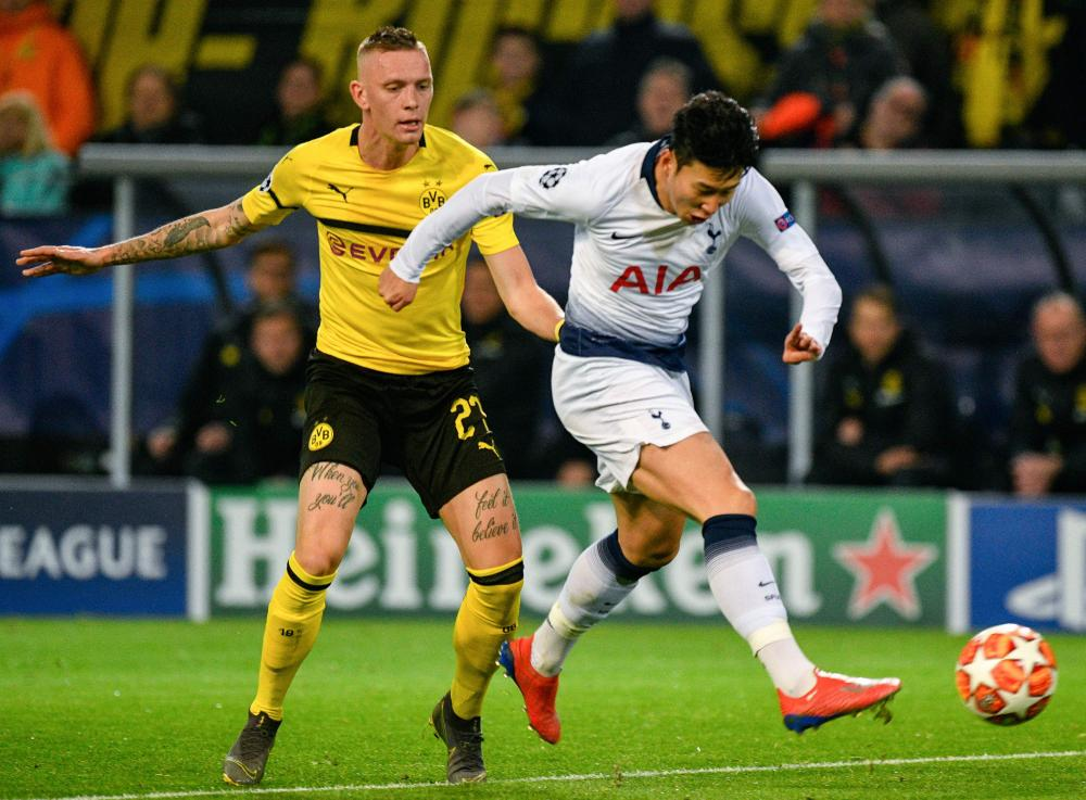 Tottenham Hotspur's Son Heung-Min gets a shot away despite the attention of Dortmund's Marius Wolf