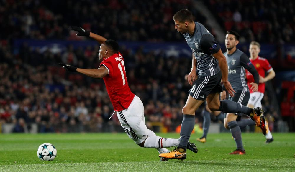 Anthony Martial is taken down by Benfica's Ruben Dias.