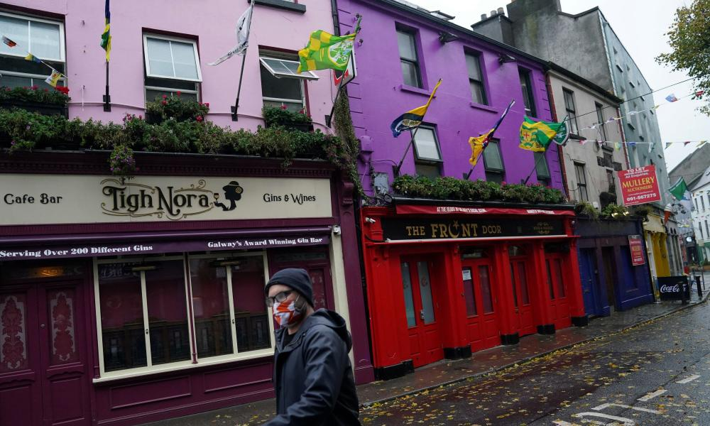 A man wearing a protective face mask walks past shuttered businesses in an empty shopping street in Galway as the government announced they were moving the country to its highest level of restrictions, Level 5, for six weeks.