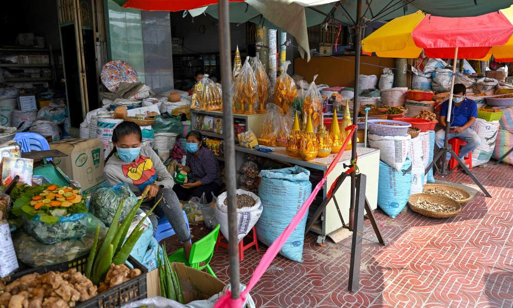 Vendors sit behind a piece of rope, used to create social distancing.