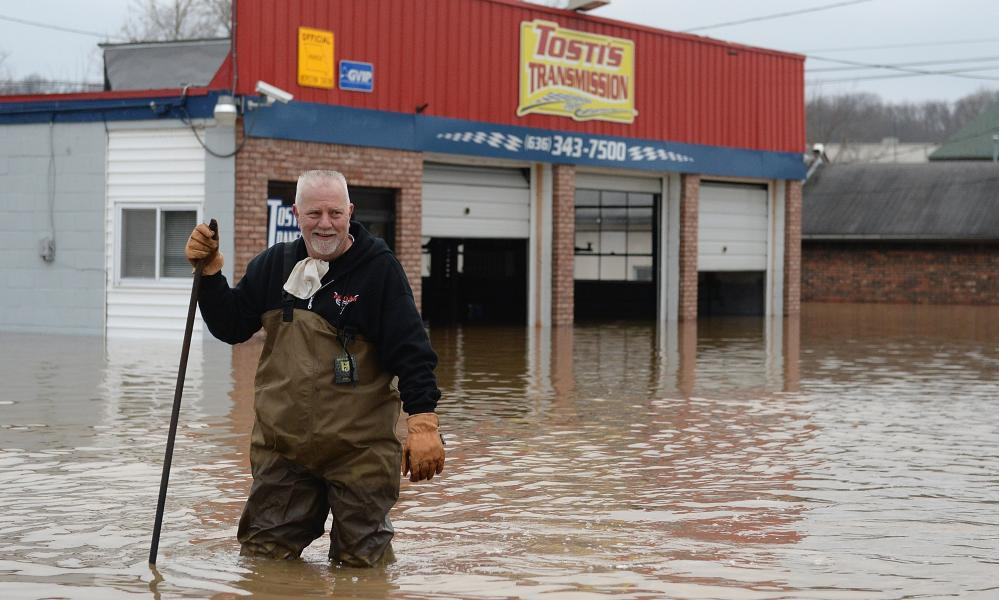 John Tosti, owner of Tosti's Transmission wades in the water after inspecting his business as it takes on floodwater on Wednesday in Fenton, Missouri.