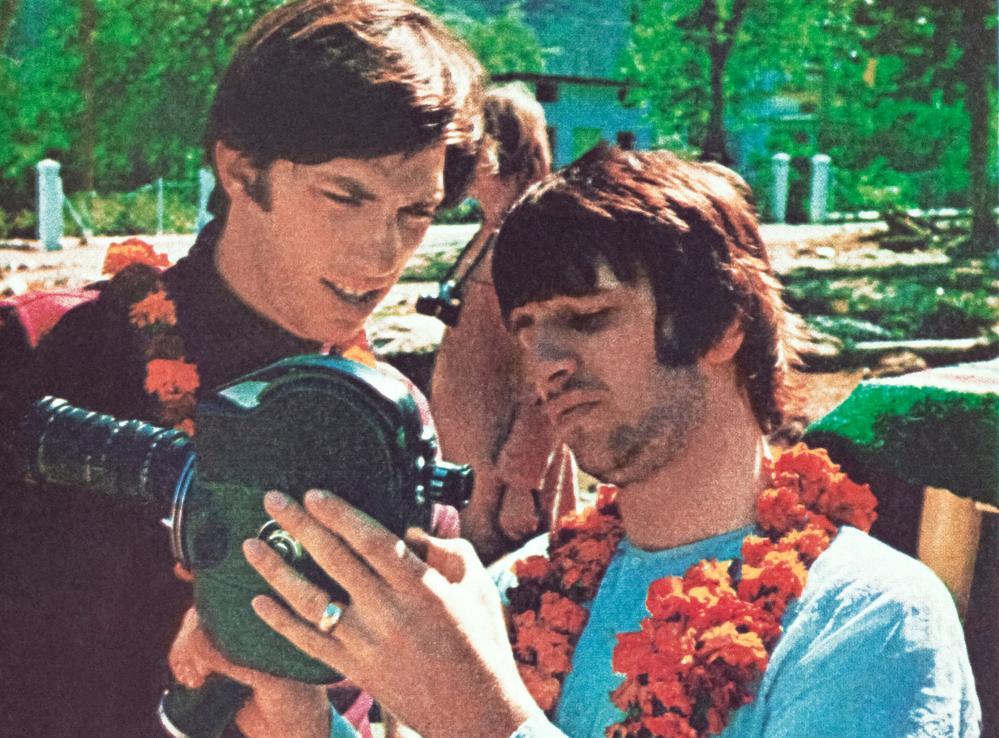 Ringo Starr shows Paul Saltzman how to use his film camera.