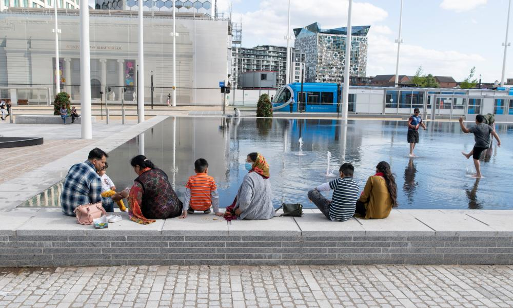 Families enjoying the water feature in Centenary Square in the city.
