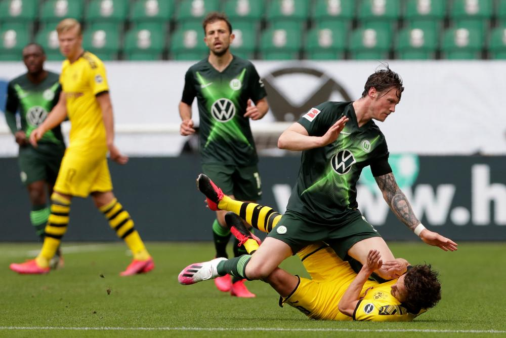 Ooff! Dortmund's Thomas Delaney is on the deck after colliding with Wolfsburg's Wout Weghorst.