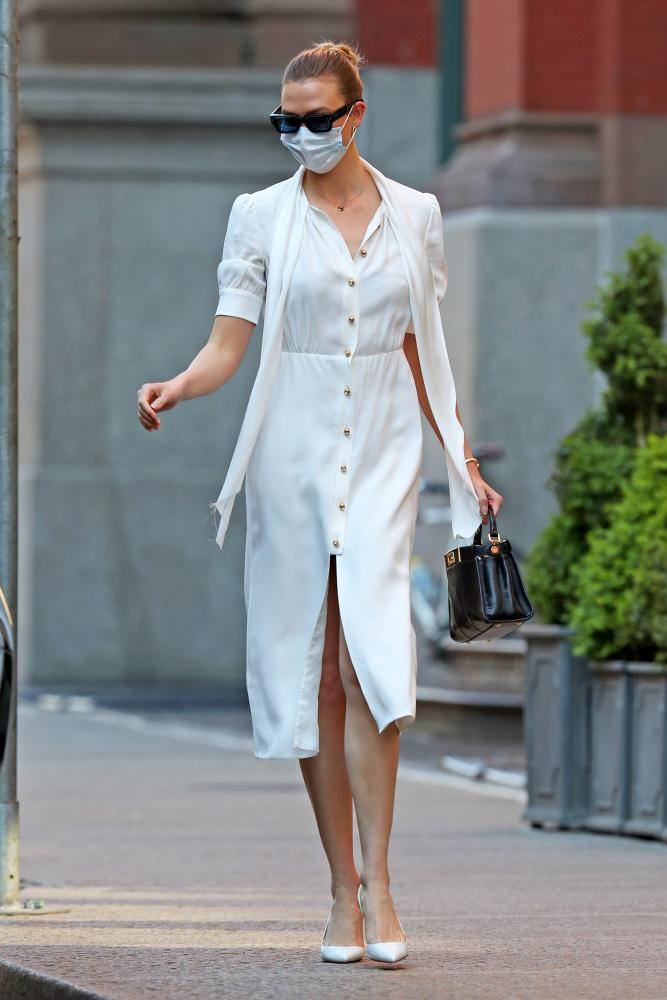 Karlie Kloss offsets her sunglasses against a white mask in New York