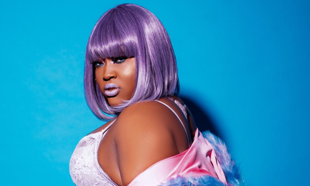 cupcakke in a purple wig looking over her shoulder into the camera