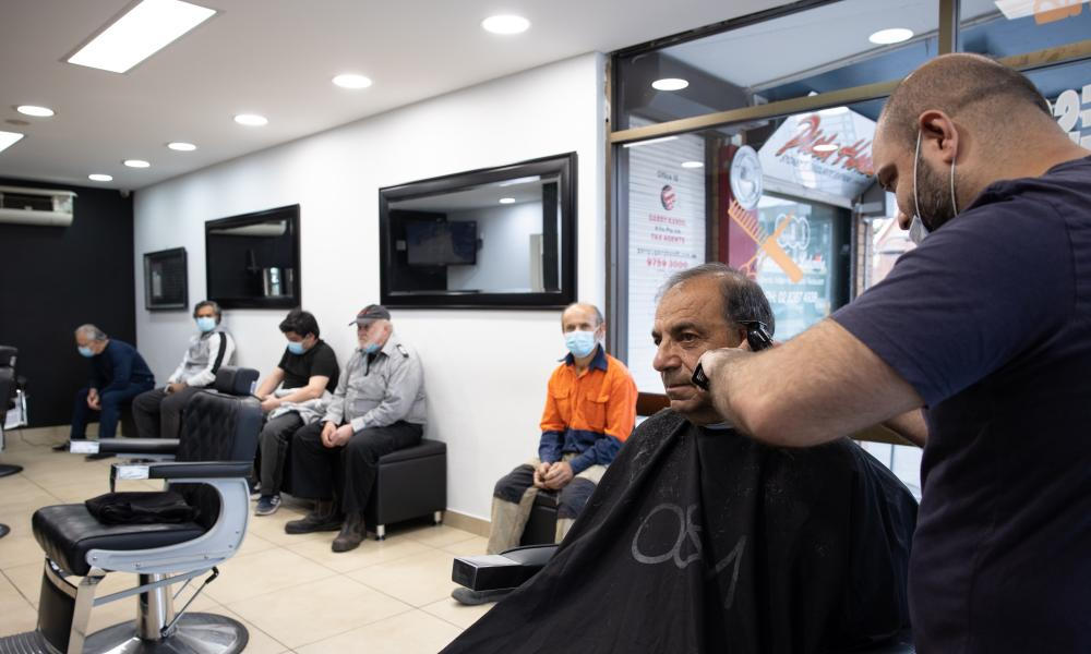 Barber Moustafa Elrifai cuts a customer's hair at his salon in Lakemba on Monday morning as greater Sydney reopened to those who have been fully vaccinated.