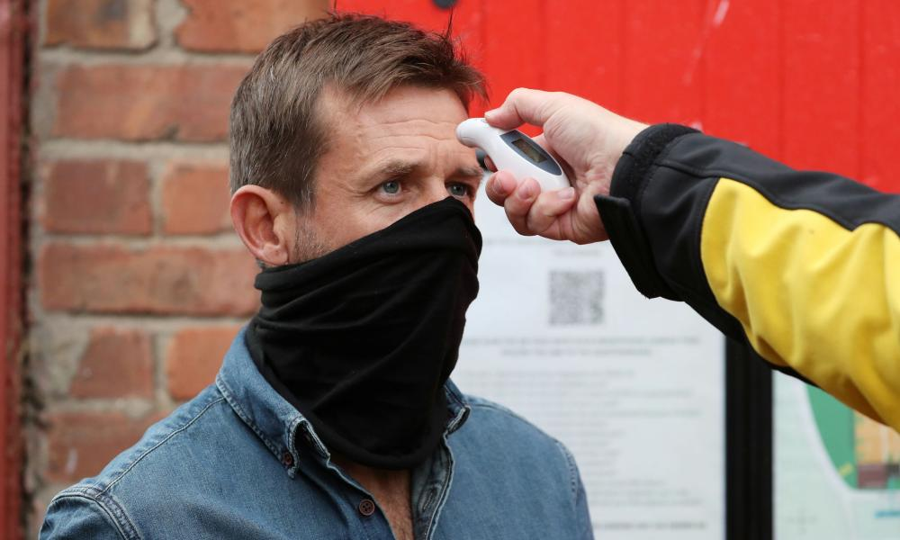 Former player Neil McCann has his temperature checked before entering the stadium.
