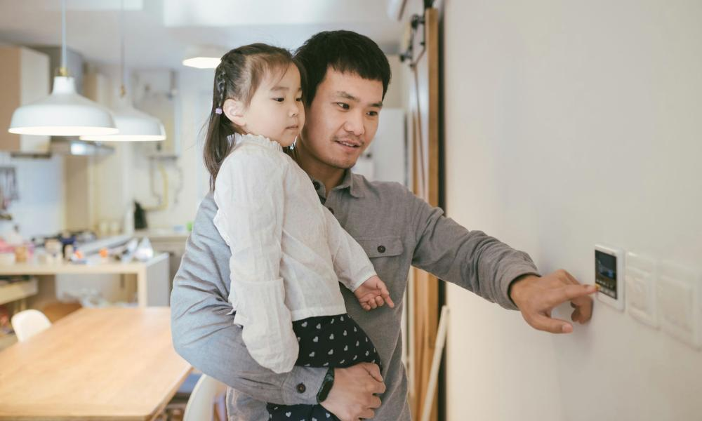 Father And Kid Adjusting The Thermostat At Home
