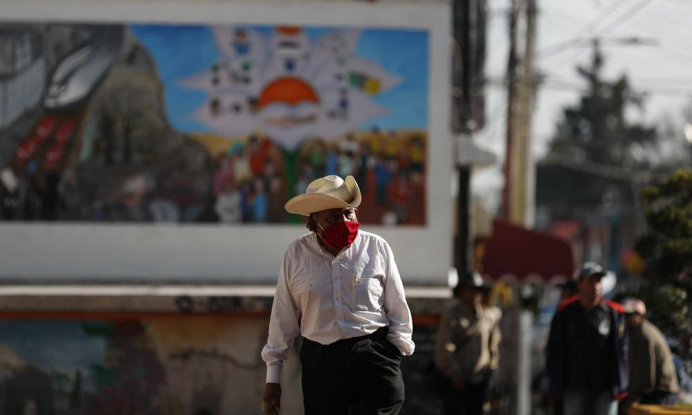 People, some wearing masks, walk in the central plaza of San Gregorio Atlapulco in the Xochimilco district of Mexico City, Wednesday, 22 July 2020.