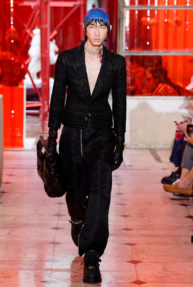 A model wearing a blazer walks the catwalk.
