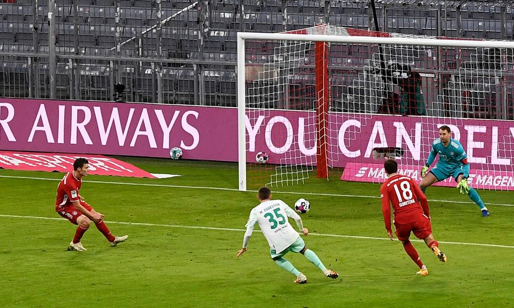 Maximilian Eggestein of Bremen scores his team's first goal against Bayern Munich keeper Manuel Neuer.