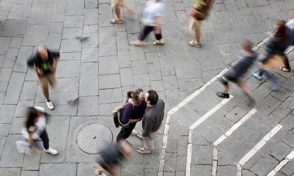 A couple kissing tenderly in the Campo, the focal point and meeting place of historical Siena