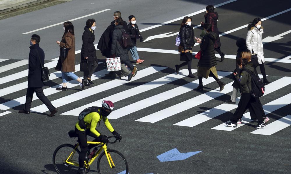 People wearing protective masks t walk along a pedestrian crossing in Tokyo