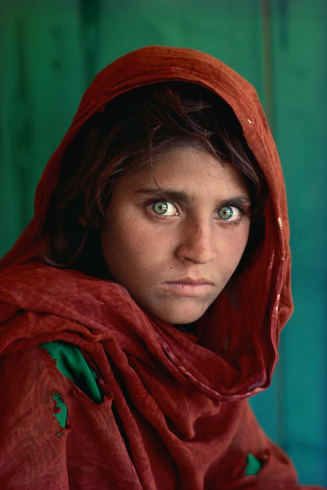 Steve McCurry's Afghan Girl. A portrait of Sharbat Gula taken at Nasir Bagh refugee camp, Pakistan in 1984 as refugees fled the country during the Afghan-Soviet conflict.