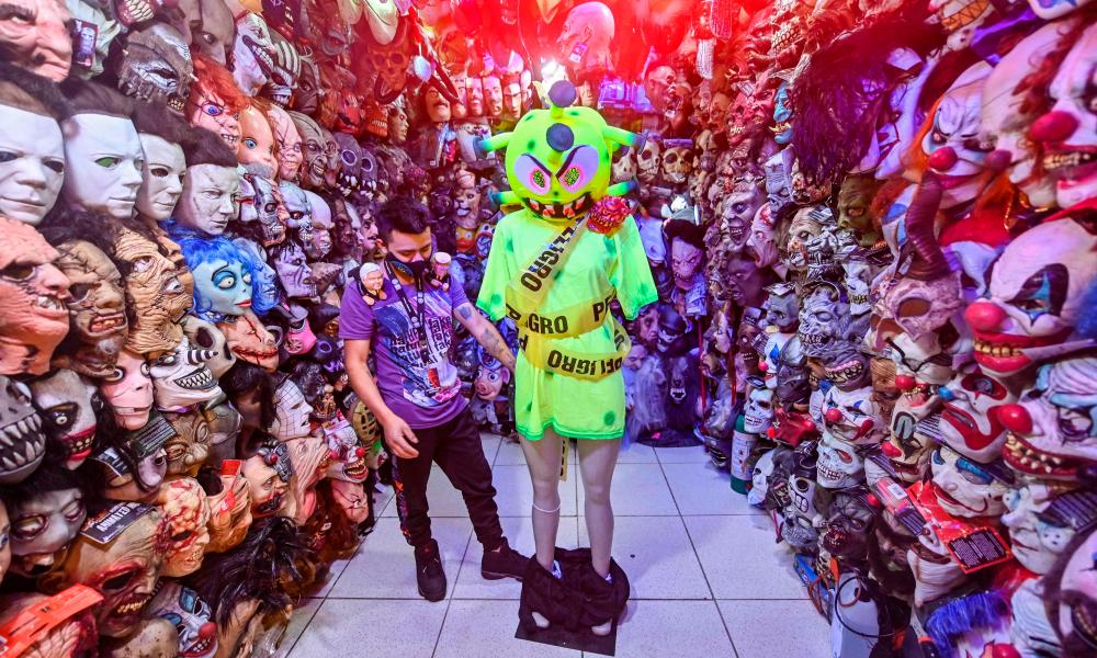 A worker puts a coronavirus suit on a mannequin at a store selling Halloween costumes in Mexico City.
