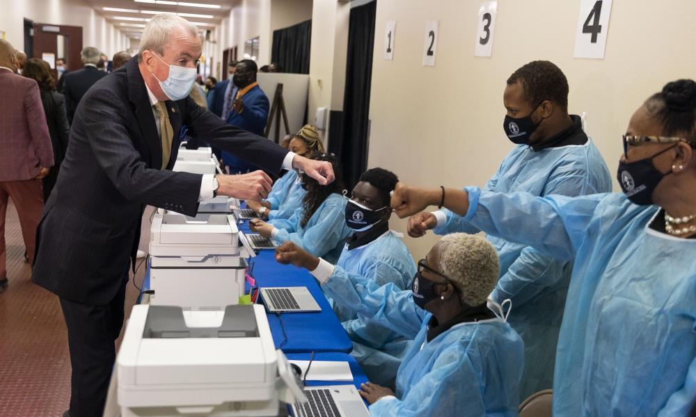 Governor Phil Murphy (Democrat of New Jersey) (L) fist bumps healthcare workers while touring a vaccination site with Vice President Kamala Harris at Essex County Community College in Newark on October 8.