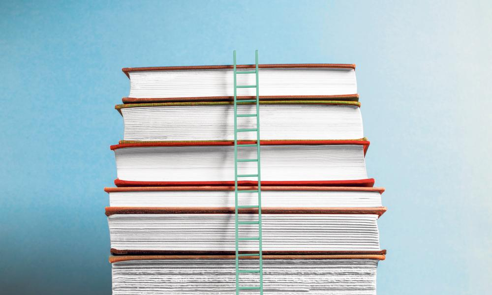 Ladder up stack of booksTall white ladder leaning on 10 vintage books on wooden table, blue background