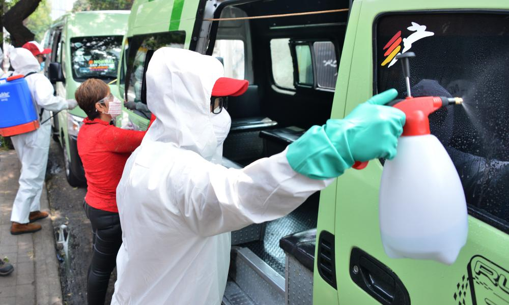 Workers spray disinfectant on public transport vehicles to curb the spread of Covid-19 in Mexico City