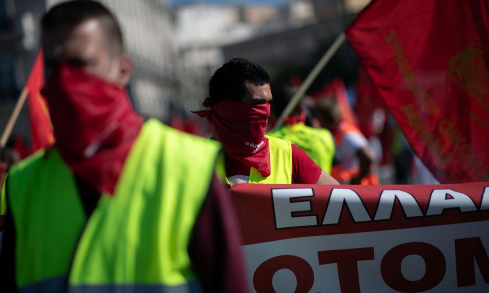 """Members of the communist-affiliated trade union PAME wear scarves reading """"The covered mouths have a voice"""" during a rally commemorating May Day, following the coronavirus disease (COVID-19) outbreak, in Athens, Greece, May 1, 2020."""