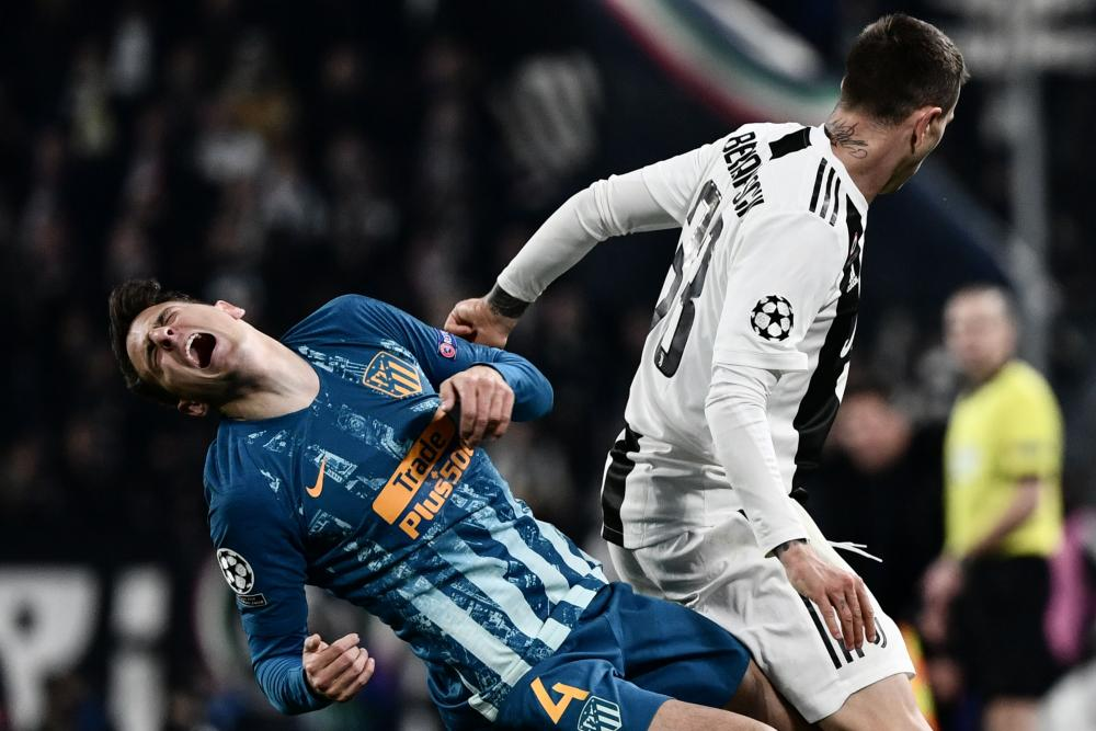 Atletico Madrid's Santiago Arias goes to ground after being caught by Juventus' Federico Bernardeschi.