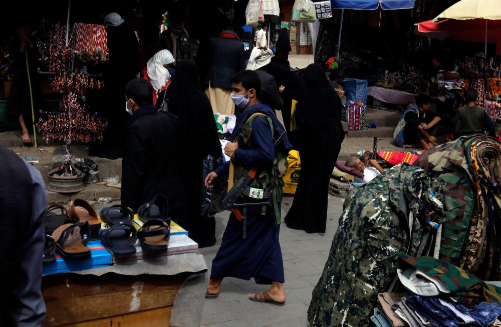 An man wearing a protective face mask and carrying a rifle walks through a market in Sanaa.