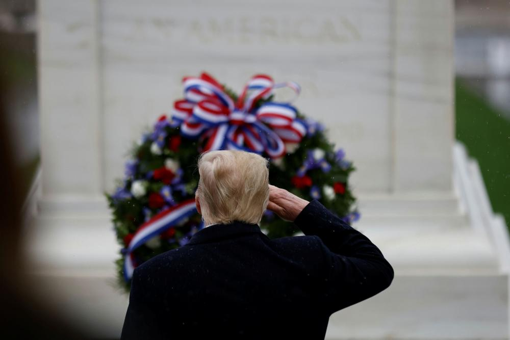 Donald Trump salutes at the Tomb of the Unknown Solider during a Veterans Day observance in Arlington National Cemetery.
