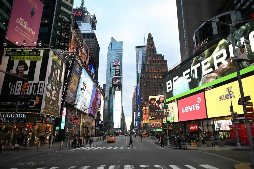 A woman wearing a mask crosses the street in Times Square in Manhattan on March 17, 2020 in New York City.
