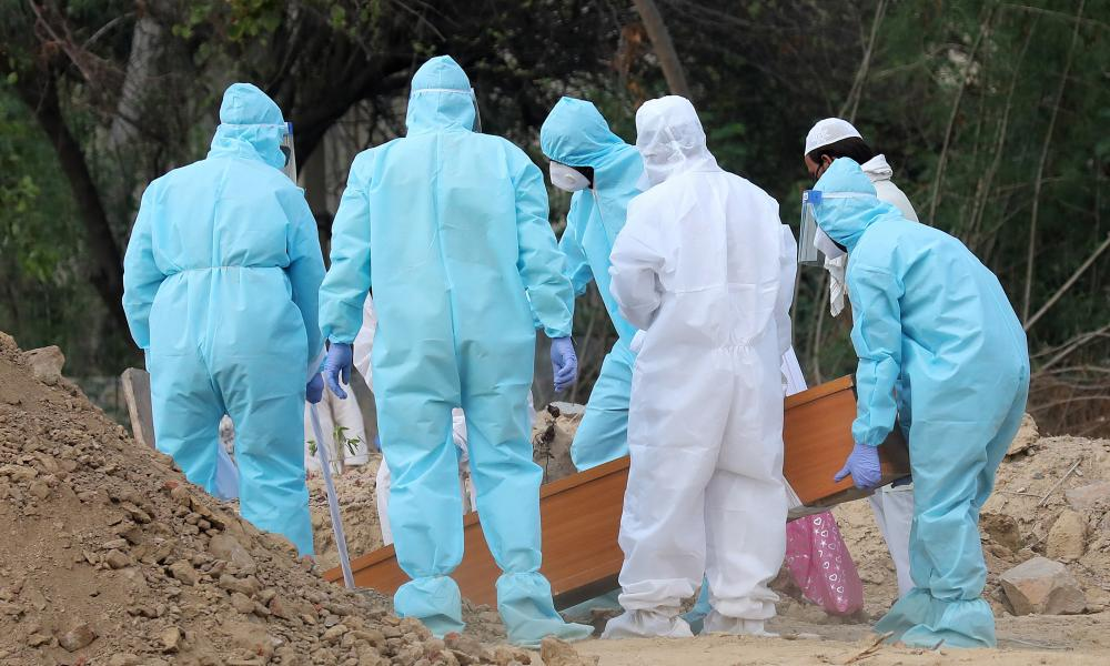 Relatives wearing personal protective equipment lower the body of a Covid-19 victim into a grave in New Delhi, India, 16 June 2020.