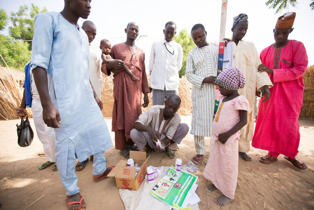 People stand watching as a local worker gets out a trachoma treatment kit, Nigeria