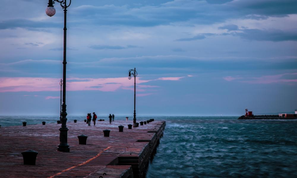A cold and windy day in the port of Trieste, Italy, as people stroll along a boardwalk.