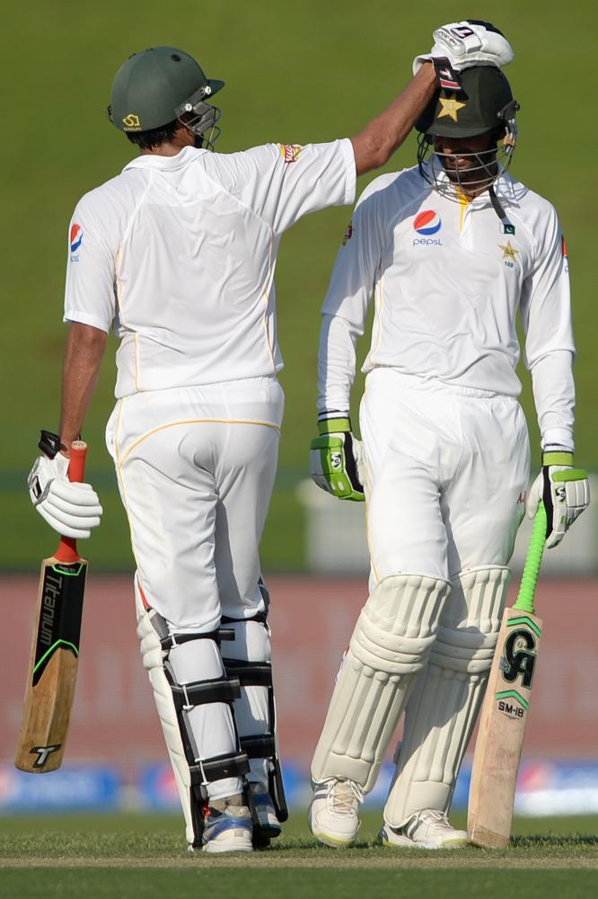 Shoaib Malik, right, is congratulated on his century by Younis Khan.