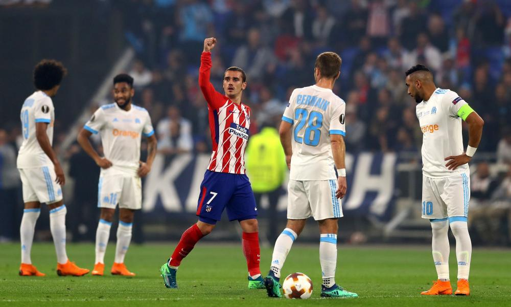 Antoine Griezmann of Atletico Madrid celebrates scoring the opening goal while Dimitri Payet of Marseille looks dejected.