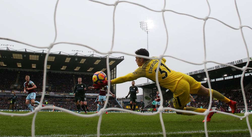 Ederson makes the save from Burnley's Ben Mee.