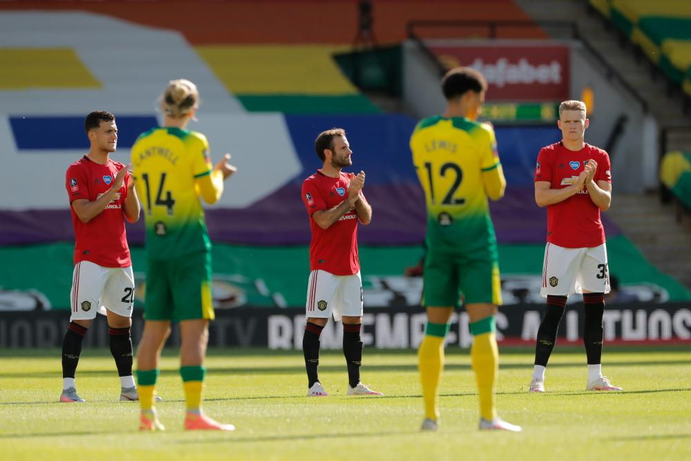 Juan Mata and his Manchester United team-mates during a minute's applause for key workers.