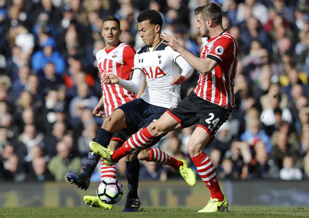 Tottenham Hotspur's Dele Alli, center, and Southampton's Jack Stephens challenge for the ball